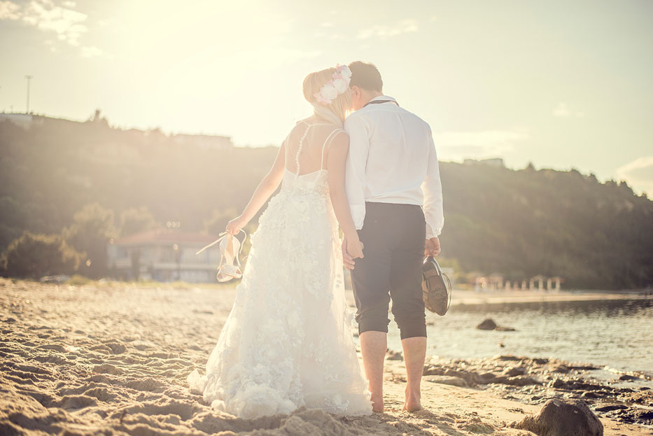 Bride-and-groom-holding-hands-on-the-beach-at-sunset-000065309045_Medium