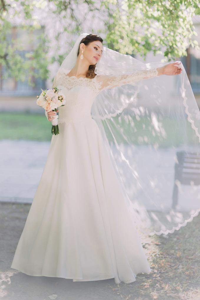 beautiful-happy-bride-spinning-around-with-veil-holding-bridal-bouquet-000092481001_medium-2
