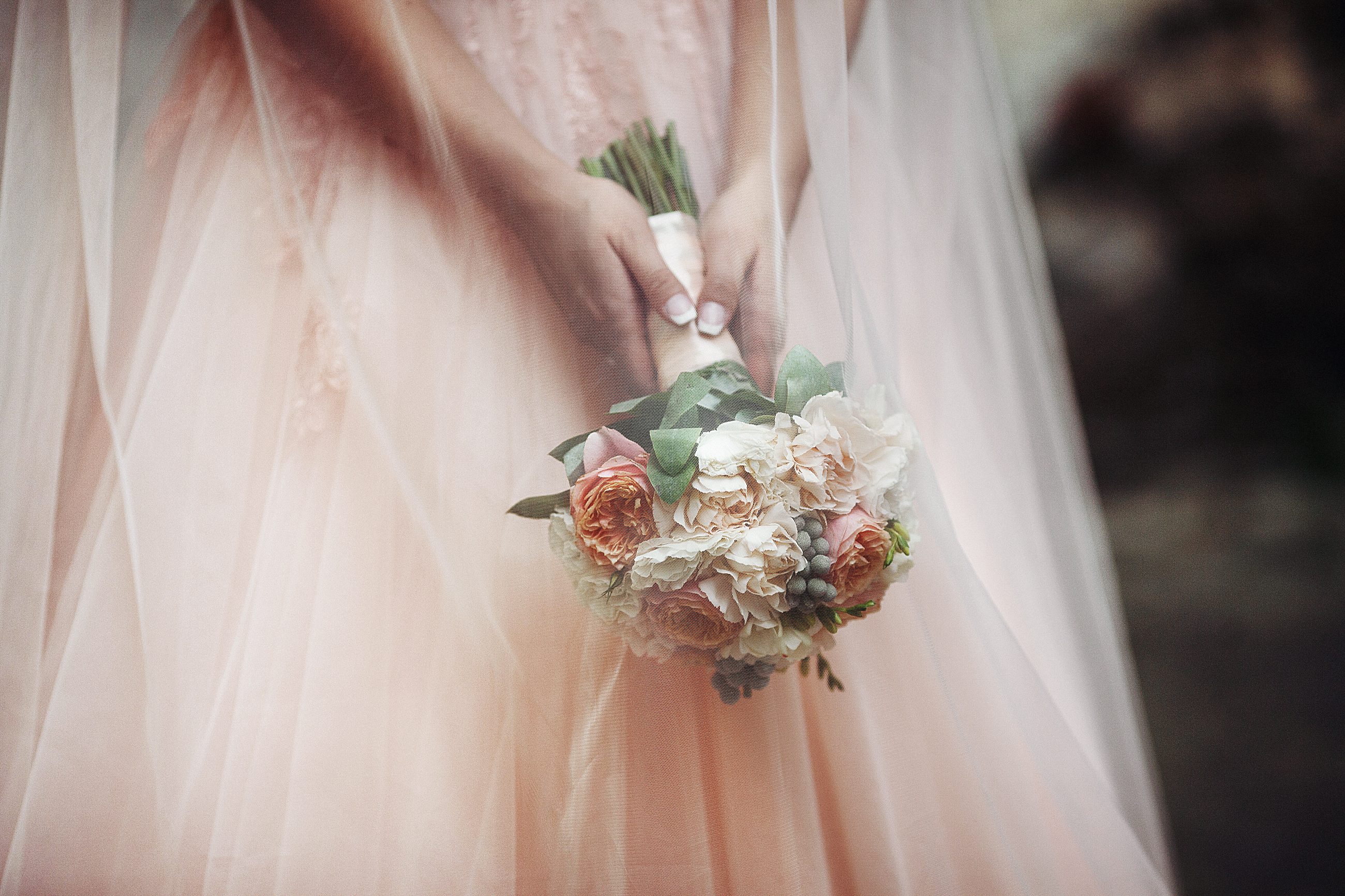 Beautiful bride in a pink dress holding a bouquet